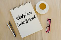 Top view of pen,sunglasses,a cup of coffee and notebook written with Workplace Harassment on wooden background. stock image
