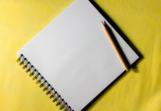 Pencil hand drawing book. Top view of pencil and drawing book on yellow background Royalty Free Stock Image