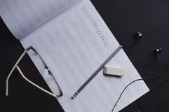 Music notes writing composer creating musician art. Top view of the pencil, eyeglasses, earphones and eraser laying on the sheet notes with handwritten notes stock image