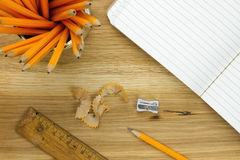 Top-view of pencils and lined paper. Top-view of pencils, lined paper, ruler and pencil sharpener on wooden surface Stock Photo