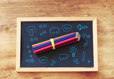 Top view of pencils stack over blackboard and various drawing Royalty Free Stock Photos