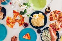 Top view of people having dinner at the table. Family eating food and having drinks. Pizza, salad, potatoes to share. Top view of people having dinner at the Royalty Free Stock Image