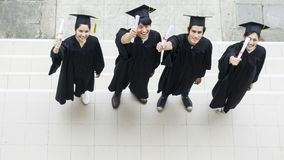 Top view of people students with the Graduation gowns and hat. Stand and hold diploma in the feeling of happy and graceful Royalty Free Stock Photography