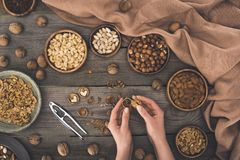 Person cracking walnut. Top view of person cracking walnut above wooden table Royalty Free Stock Photography