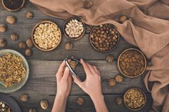 Person cracking walnut. Top view of person cracking walnut with nutcracker above wooden table Stock Photography