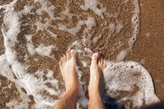 Top view of person feet in water on sandy beach and waves. Summer vacation concept. Relaxing at ocean shore stock image