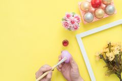 Top view person painting colorful easter egg painted in pastel colors composition with paint brush on yellow pastel colour. Top view person painting colorful Royalty Free Stock Photo