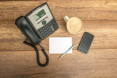 Top view of phone, blank paper, pen, coffee and a smart phone Royalty Free Stock Photos