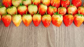 Top view photo, a heap of fresh berry fruit, red strawberry on wooden background with coppy space stock image