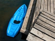 Top view photo of kayak near plank pier. Small plastic rowing boat azure color designed for kids. Top view photo of kayak near plank pier stock photos