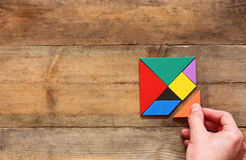 Top view photo of man's hand holding a missing piece in a square tangram puzzle, over wooden table. Royalty Free Stock Photography
