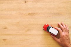 Top view photo of man& x27;s hand holding toy car over wooden background. Top view photo of man& x27;s hand holding toy car over wooden background Stock Photos