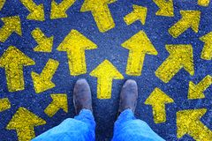Top view photo of person in jeans and retro shoes standing over asphalt road with painted arrows showing different directions. Filtered royalty free stock photos