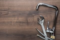 Top view photo of plumbing tools over wooden background with copy space.