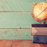 Top view photo of vintage globe and stack of books on wooden desk. vintage filtered image Royalty Free Stock Photos