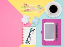 Top view photo of workspace with smartphone, coffee cup and open notepad on pastel background. Pastel color working desk. Royalty Free Stock Photography