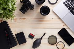 Top view of photographer desk with latptop, camera, lenses and accessories with copy space. Flat lay shot on wooden background stock photos