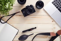 Top view of photographer desk with latptop, camera, lenses and accessories with copy space royalty free stock images