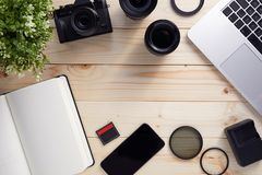 Top view of photographer desk with latptop, camera and lenses with copy space royalty free stock photos