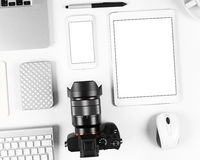 Top view of photographer workplace: Keyboard, tablet, camera and smartphone on white desk background Royalty Free Stock Images