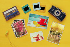 Top view of photographs next to old camera. Over yellow wooden table. Flat lay stock images