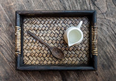 Top view photography of mini jar of syrup and wooden spoon all t. Ogether put in bamboo tray Royalty Free Stock Photography
