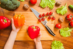 Top View Picture of Hands on tableboard with vegetables holding Stock Images