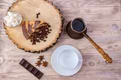 Top view of a piece of chocolate cake on wooden stump with a coffee cup, tea spoon, fork, anise, coffee beans, chocolate bar and b. Owl with sugar cubes on a Stock Photography