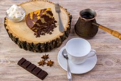 Top view of a piece of chocolate cake on wooden stump with a coffee cup, tea spoon, fork, anise, coffee beans, chocolate bar and b. Owl with sugar cubes on a Stock Photo