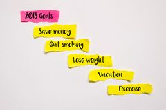 Top view of piece of sheet of pink and yellow paper with words 2018 goals,save money,quit smoking,lose weight,exercise,and vacatio. N on a white background Stock Image