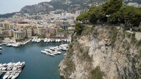 Top view of pier with parked yachts on sea. Action. Beautiful landscape view from rocky coast to seaside town with port. For yachts. Expensive yachts moored on stock footage