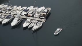 Top view of pier with parked yachts on sea. Action. Motorboat sails near marine Parking lot of expensive white yachts at. Pier. Maritime transport in South stock video footage