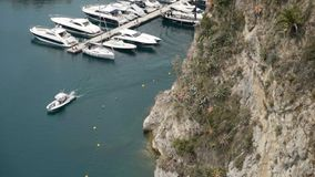 Top view of pier with parked yachts on sea. Action. Motorboat sails near marine Parking lot of expensive white yachts at. Pier. Maritime transport in South stock video