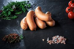 Top view on pile of short sausages with rucola and tomatoes. Top view pile on short thick sausages with pink salt, spices, green rucola and tomatoes cherry on stock photo