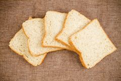 Pile slice of whole wheat bread on dark brown calico. stock photography