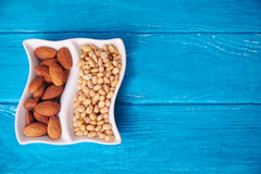 Top view at pine nuts and almond in wave plate Royalty Free Stock Image