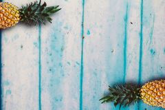 Ripe pineapples over the blue wooden table. royalty free stock image