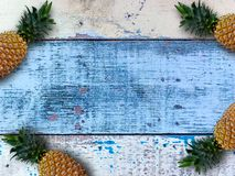 Ripe pineapples over the blue wooden table. stock photography