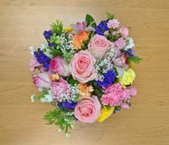 Top view of pink flower bouquet on a wooden board. The colorful bouquet has many kinds of flowers, roses, Carnation.  a good gift for any celebration and happy Royalty Free Stock Photo