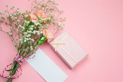 Pink gift box, bouquet of flowers with mock up empty label. Top view pink gift box, bouquet of flowers with mock up empty label royalty free stock photography