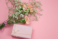 Pink gift box and flowers. Top view pink gift box and flowers on a pastel pink background stock photo