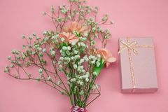 Pink gift box and flowers on a pastel pink background. Top view pink gift box and flowers on a pastel pink background stock image