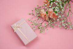 Pink gift box and flowers on a pastel pink background. Top view pink gift box and flowers on a pastel pink background royalty free stock photos
