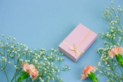 Pink gift box and flowers on a pastel blue background. Top view pink gift box and flowers on a pastel blue background royalty free stock photography