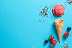 Top view of a pink icecream scoop in a waffle cone with strawberries, black berries, and colorful, rainbow sprinkles on a blue ba royalty free stock photography