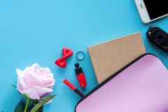 Top view of pink lady bag with diary book, pen, lipstick, bow, ring, car key, smartphone and sweet rose on blue background. For women accessories and lady royalty free stock photos