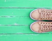 Top view of a pink pair of female leather sneakers. With laces on a green wooden background, copy space stock images