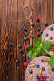 Top view of a pink smoothie. A close-up of a sweet yogurt on a wooden background. Smoothie with raspberries, blueberries and mint. A view from above on pink Royalty Free Stock Image