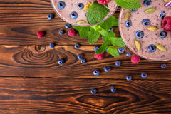 Top view of a pink smoothie. A close-up of a sweet yogurt on a wooden background. Smoothie with raspberries, blueberries and mint. Royalty Free Stock Photography