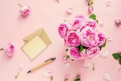 Top view pink tea roses bouquet,blank of greeting card and craft paper envelope, pen on pink background. Postcard mock up. Summer,. Spring flowers. Flat lay royalty free stock photo